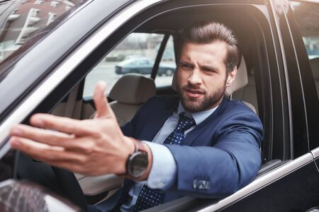 Foto de I dont like it. Angry and emotional businessman in formal wear is gesturing and making a grimace while driving his car. - Imagen libre de derechos