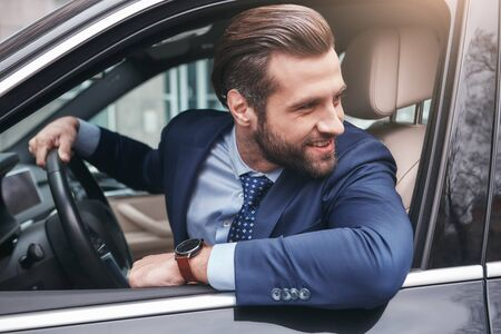 Photo for Happy driver. Happy and stylish young businessman in full suit is looking through the window and smiling while sitting in his comfortable car. - Royalty Free Image
