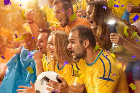 Photo pour Fun soccer Fans in stadium arena Confetti and tinsel - image libre de droit
