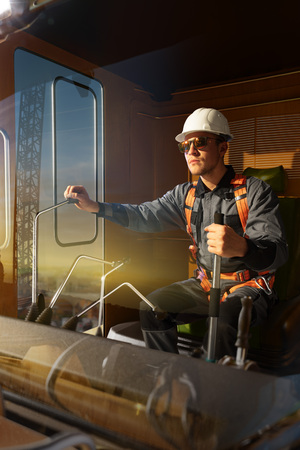 Photo for Engineer operator crane in action . He sit a top in crane cabin and working. Around beautiful sunset - Royalty Free Image