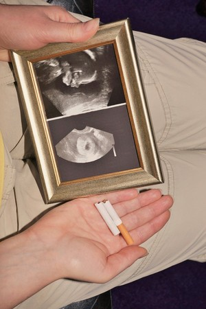 Photo pour Pregnant woman with ultrasound and broken cigarette in her hand - image libre de droit