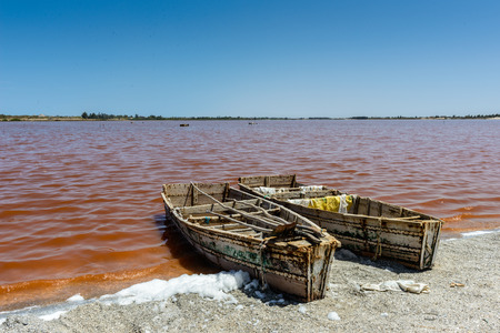 Foto per Sailman's boat over the pink water lake in Senegal, Africa - Immagine Royalty Free