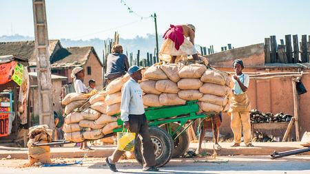 Foto de ANTANANARIVO, MADAGASCAR - JUNE 27, 2011: Unidentified Madagascar woman stays over the bags on a carriage. People in Madagascar suffer of poverty due to the slow development of the country - Imagen libre de derechos