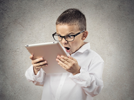 Photo pour Closeup portrait child, shocked, surprised, funny looking boy with glasses using, holding laptop, pad computer isolated grey, black background  Human face expressions, emotions, reaction body language - image libre de droit