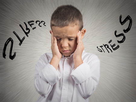 Foto de Closeup portrait stressed child, boy hands on temples, head spinning around, overwhelmed at school in life, isolated grey wall background  Human facial expressions, emotions, feeling, perception - Imagen libre de derechos