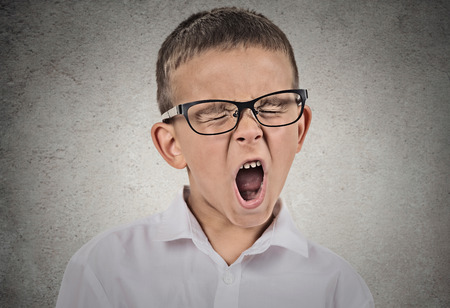 Foto de Closeup portrait tired child with glasses yawning, isolated on grey wall background. Human facial expressions, emotions, feelings, body language. Long school hours, busy day concept. - Imagen libre de derechos