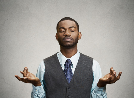Young businessman meditating, eyes closed, isolated grey wall background. Stress relief techniques at work concept. Take a deep breath.
