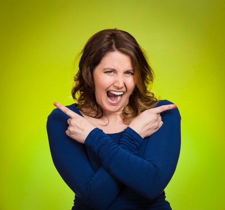 Portrait confused young woman pointing in two different directions, stressed, frustrated, screaming, overwhlemed, not sure which way to go in life isolated green background. Negative emotion facial expression feeling body language