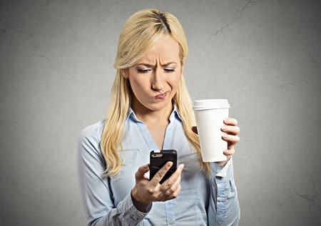 Closeup portrait serious worried business woman reading bad news on smart phone holding mobile drinking cup of coffee isolated grey wall background. Human face expression, corporate executive emotions