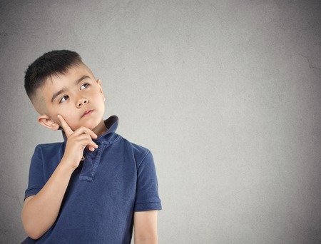 Foto de Aspirations. Closeup portrait, headshot thinking, daydreaming child boy finger on face, looking up, isolated grey wall background. Positive human facial expression, emotions, feeling life perception - Imagen libre de derechos