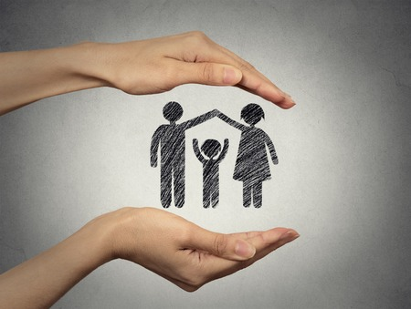Foto de close up of woman's hands protecting happy family, mother, father, child. Family abstract in palms on grey wall background. Safe childhood, parenting. Love care compassion safety secure future concept - Imagen libre de derechos