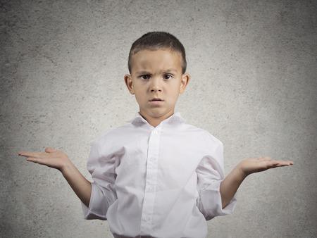 Foto de Closeup portrait clueless, unhappy child boy with arms out asking what - Imagen libre de derechos