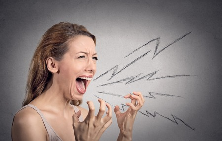 Foto de Side view portrait angry woman screaming, wide open mouth, hysterical isolated grey wall background. Negative human face expressions, emotion, bad feelings reaction. Conflict, confrontation concept - Imagen libre de derechos