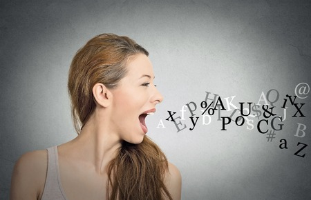 Photo pour Side view portrait woman talking with alphabet letters coming out of her open mouth isolated grey wall background. Human face expressions, emotions. Communication, information, intelligence concept - image libre de droit