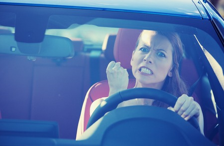 Photo pour Portrait displeased angry pissed off aggressive woman driving car, shouting at someone in traffic hand fist up in air front windshield view. - image libre de droit