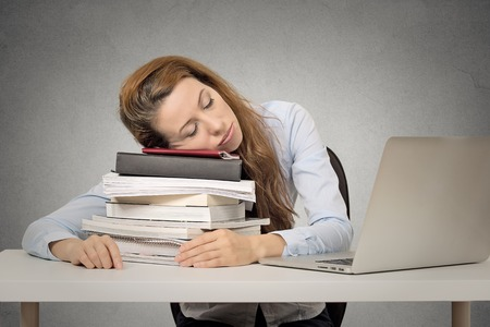 Foto de Too much work tired woman sleeping on books at her desk in front of computer isolated on grey wall office background. Busy schedule in college, workplace, sleep deprivation concept - Imagen libre de derechos