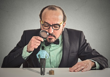 Foto de Curious corporate businessman skeptically meeting looking at small employee standing on table through magnifying glass isolated office grey wall background.  - Imagen libre de derechos