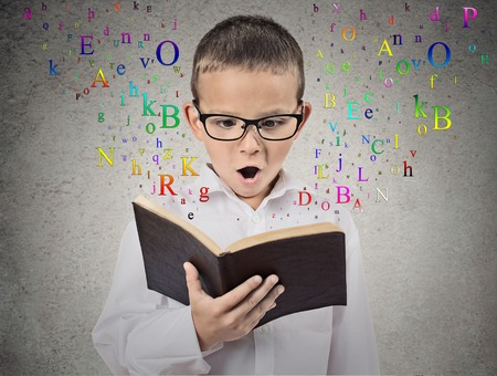 Photo pour Surprised child reading a book with letters flying away from it isolated on grey wall background. Face expression. Education concept - image libre de droit