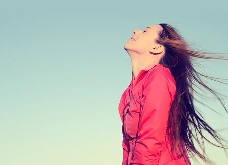 Foto de Woman smiling looking up to blue sky taking deep breath celebrating freedom. Positive human emotion face expression feeling life perception success peace mind concept. Free Happy girl enjoying nature - Imagen libre de derechos