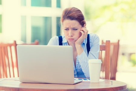 Photo for Portrait young stressed displeased worried business woman sitting in front of laptop computer isolated outdoors city background. Negative face expression emotion feelings problem perception - Royalty Free Image