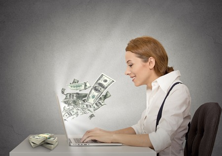 Foto de Side profile happy smiling business woman working online on computer earning money dollar bills banknotes flying out of laptop screen isolated grey wall office background. Human face expression - Imagen libre de derechos