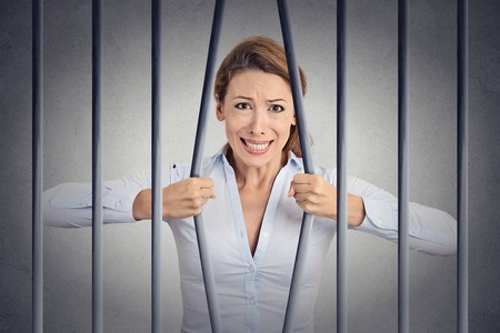 Foto de Stressed desperate angry businesswoman bending bars of her prison cell grey wall background. Life limitations, law violation infringement tax evasion consequences concept. Face expression emotion - Imagen libre de derechos