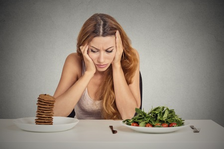 Foto de Young woman tired of diet restrictions deciding whether to eat healthy food or sweet cookies she is craving sitting at table isolated grey background. Human face expression emotion. Nutrition concept - Imagen libre de derechos