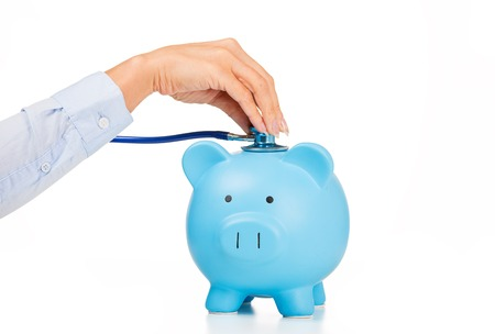 Foto de Piggy bank and stethoscope Isolated on white background. Health care cost. Financial state condition self assessment concept. Financial system checkup or saving for medical insurance costs - Imagen libre de derechos