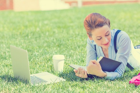 Photo for Student studying in park. Joyful happy young girl student sitting reading book outside on university campus or park. Education concept. Positive face expression - Royalty Free Image