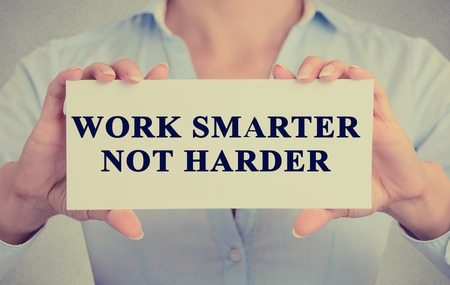 Foto de Work Smarter Not Harder Concept. Closeup retro style image business woman hands holding card with motivational message phrase text written on it isolated grey office wall background - Imagen libre de derechos