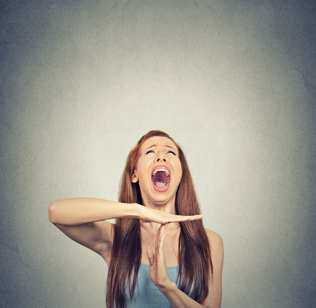 Foto de Young woman showing time out hand gesture, frustrated screaming to stop isolated on grey wall background. Too many things to do. Human emotions face expression reaction - Imagen libre de derechos