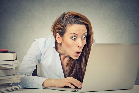 Foto de Portrait young shocked business woman sitting in front of laptop computer looking at screen isolated grey wall background. Funny face expression emotion feelings problem perception reaction - Imagen libre de derechos