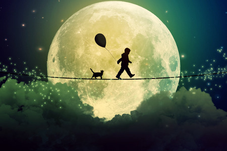 Foto de Happy boy teenager and cat walking with balloon on a tight rope above clouds with moonlight moon background. Happiness care free concept.  - Imagen libre de derechos