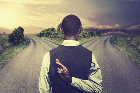 Photo pour businessman in front of two roads crossing fingers hoping for best taking chance - image libre de droit