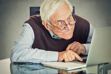Foto de Elderly old man using computer sitting at table isolated on grey wall background. Senior people and technology concept - Imagen libre de derechos