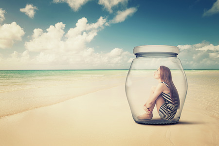 Foto de young woman sitting in a glass jar on a beach looking at the ocean view. Loneliness outlier person. After storm survivor message to future generation concept - Imagen libre de derechos