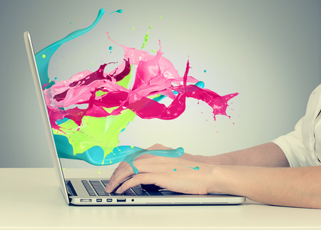 Foto de Closeup portrait of business woman's hands on keyboard using laptop with colorful splashes, liquid effect out of monitor screen computer display  isolated on gray background. Creative business concept - Imagen libre de derechos