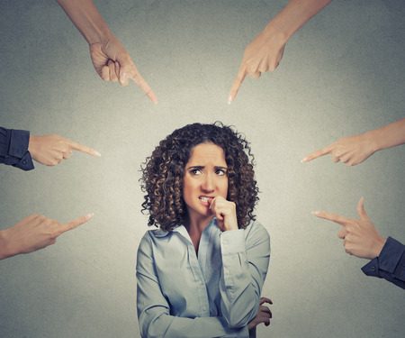 Foto de Concept of social accusation of guilty businesswoman many fingers pointing at isolated on grey office wall background. Portrait scared anxious embarrassed woman biting fingernails - Imagen libre de derechos