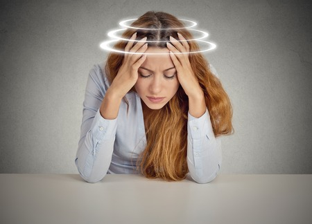 Foto de Woman with vertigo. Young female patient suffering from dizziness. - Imagen libre de derechos