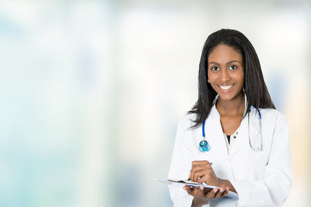 Foto de Portrait confident African American female doctor medical professional writing patient notes isolated on hospital clinic hallway windows background. Positive face expression - Imagen libre de derechos