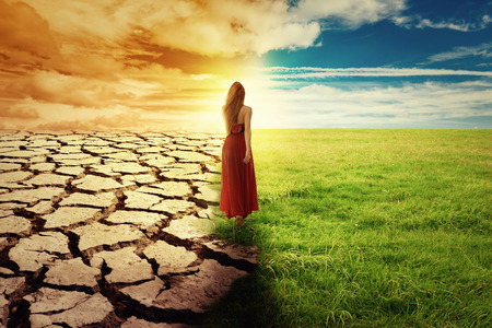 Foto per A Climate Change Concept Image. Landscape of a green grass and drought land. Woman in green dress walking through an opened field - Immagine Royalty Free