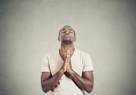 Photo pour Closeup portrait young man praying hands clasped hoping for best asking for forgiveness or miracle isolated gray wall background. Human emotion facial expression feeling - image libre de droit