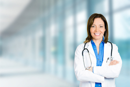 Foto de Portrait confident mature female doctor medical professional standing isolated on hospital clinic hallway windows background. Positive face expression - Imagen libre de derechos