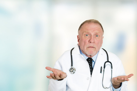 Foto de Closeup portrait clueless senior health care professional doctor with stethoscope, has no answer, doesn't know right diagnosis standing in hospital hallway isolated clinic office windows background. - Imagen libre de derechos
