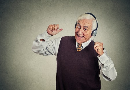 Foto de Closeup portrait elderly man, senior retired guy with headphones listening to the radio, enjoying music and his life isolated on gray wall background. Positive human emotions, face expression - Imagen libre de derechos