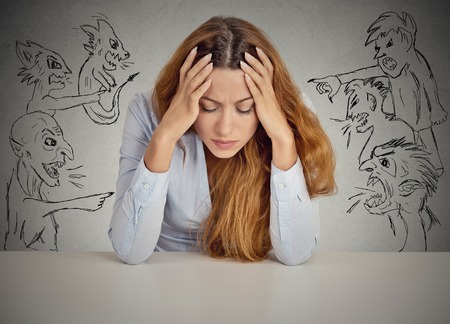 Photo for Evil Men pointing at stressed woman. Desperate young businesswoman sitting at desk in her office isolated on grey wall background. Negative human emotions face expression feelings life perception - Royalty Free Image