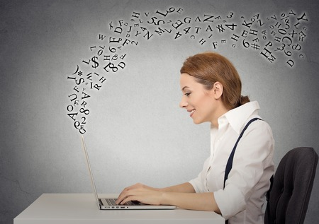 Photo for Side profile business woman sitting at desk in her office working on a laptop computer, typing with alphabet letters flying up - Royalty Free Image