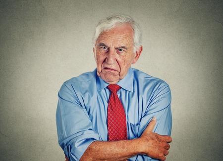 Foto de Portrait of unhappy grumpy pissed off senior mature man isolated on gray wall background. Negative human emotions, face expression feelings - Imagen libre de derechos