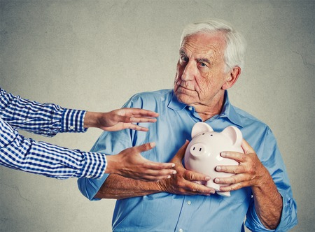 Photo for Closeup portrait senior man grandfather holding piggy bank looking suspicious trying to protect his savings from being stolen isolated on gray wall background. Financial fraud concept - Royalty Free Image
