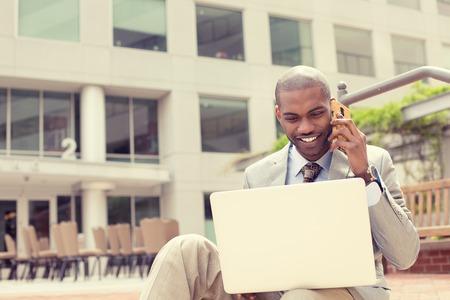 Foto de Handsome young businessman working with laptop outdoors talking on mobile phone.  - Imagen libre de derechos